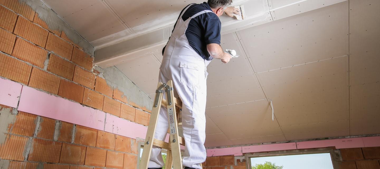 Mann steht auf einer Leiter und spachtelt die Decke