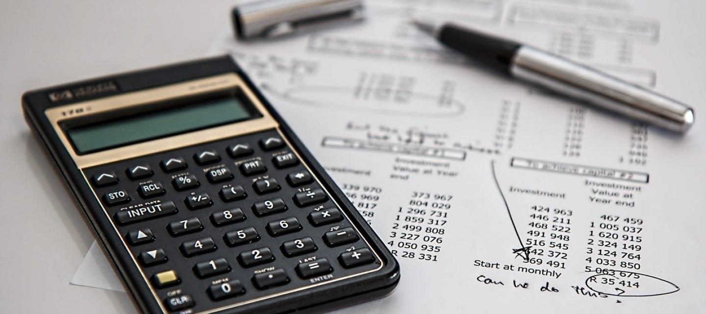 Taschenrechner auf weißem Block mit schwarzen Berechnungen